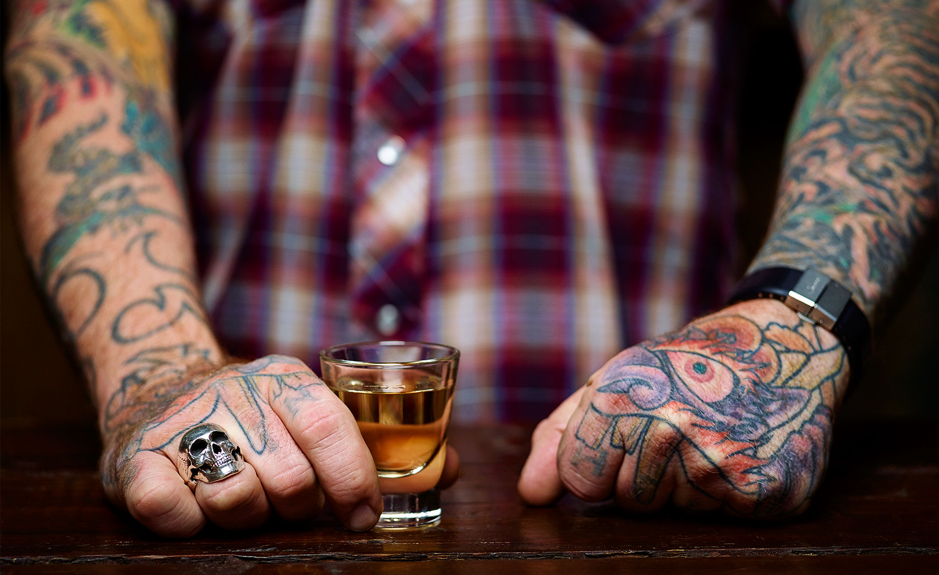 A colorful display of tattoos serving you a shot of Mezcal